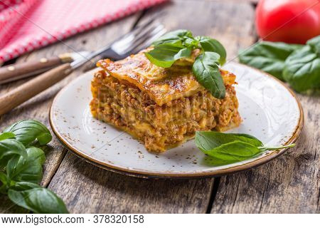 Meat Lasagna With Fresh Basil And Parmesan Cheese In A Plate On Wooden Table. Close Up. Italian Lasa