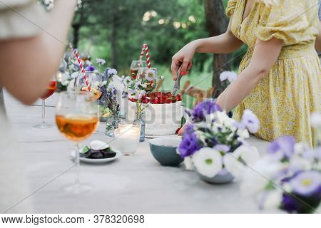 Unrecognizable Female In Dress Cutting Sweet Cake On Banquet Table During Holiday Celebration On Sum
