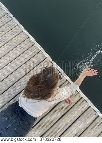 Top View Of Unrecognizable Young Female Lying On Quay And Splashing Clean Water Of Lake On Summer Da