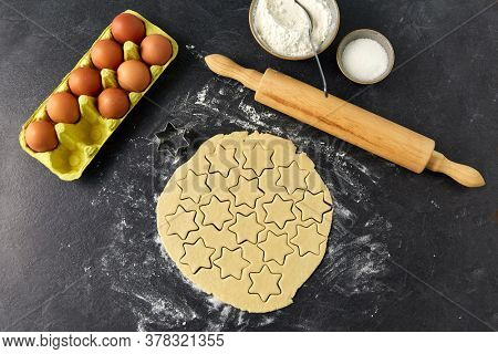cooking food and culinary concept - shortcrust pastry dough, rolling pin, eggs, flour and sugar on table