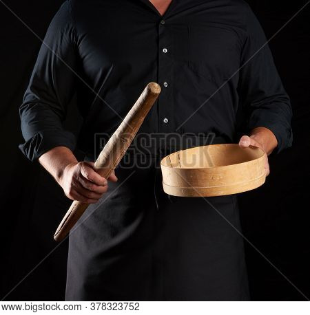 Man In Black Uniform Holding Empty Vintage Round Wooden Sieve For Sifting Flour And Rolling Pin, Che