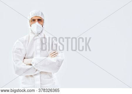 Confident Doctor With Crossed Arms In Protective Medical Suit With Copy Space On White Background