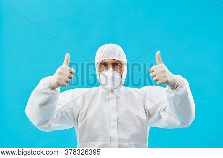Doctor In Protective Medical Suit Showing Thumbs Up On Blue Background. Success Concept