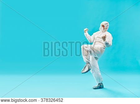 Happy Doctor In Ppe Suit Celebrating The Victory Over The Coronavirus On Blue Background With Copy S