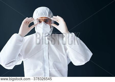 Doctor In Ppe Wearing Protective Glasses On Black Background. Healthcare Concept