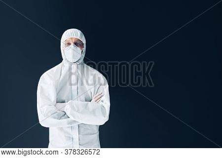 Confident Doctor With Crossed Arms In Protective Medical Suit With Copy Space On Black Background
