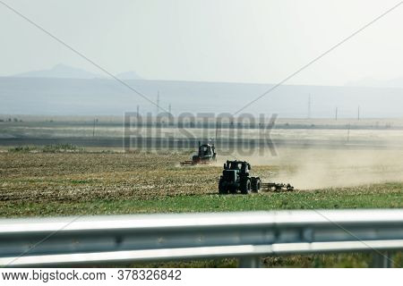 Russia, Crimea, September 11, 2019: A Tractor Plows A Field. Steppes In The Crimea. Landscape View O