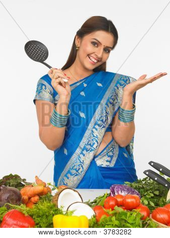 A Smiling  Woman With A Cooking Ladle
