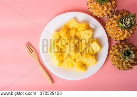 Sliced Pineapple Fruit On White Plate With Fork Ready To Eating On Pastel Pink Background, Tropical