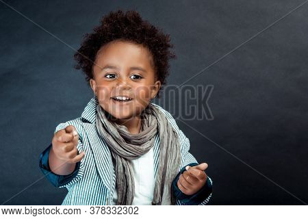Studio Portrait of a Stylish Little African Boy with Curly Hair Isolated on Dark Background. Kids Fashion. Kids Clothes.