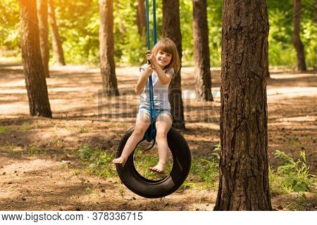 Happy Active Child Girl Playing On Swing Wheel In Forest On Sunny Summer Day. Preschool Child Having