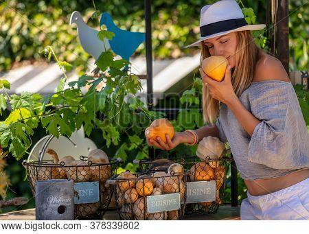 Healthy Woman at Outdoor Farmers Market.  Enjoying Aroma of a Fresh Ripe Little Pumpkin. Vegetarian Nutrition. Healthy Lifestyle.