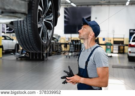 Side View Of Technician In Overalls And Cap Looking At Car Tire And Holding Gloves