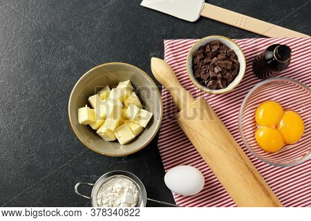 cooking food and culinary concept - rolling pin, butter, eggs, flour and chocolate on table