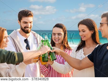 travel, tourism and friendship concept - group of happy friends toasting non alcoholic drinks over tropical beach background in french polynesia