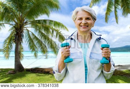 fitness, sport and healthy lifestyle concept - happy smiling senior woman with dumbbells exercising over tropical beach background in french polynesia