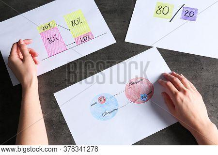 Woman Explaining 80/20 Rule At Grey Table, Top View. Pareto Principle Concept