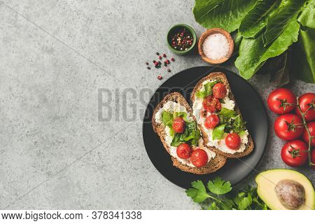 Healthy Vegetarian Bruschetta Or Toast With Roasted Tomatoes And Ricotta Cheese On A Black Plate, To