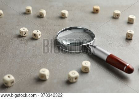 Magnifier Glass And Cubes With Letters On Light Grey Stone Background, Closeup. Find Keywords Concep
