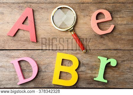 Different Color Letters And Magnifier Glass On Wooden Background, Flat Lay. Find Keywords Concept