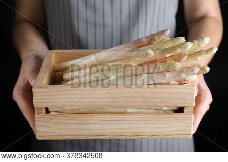Woman Holding Wooden Crate With Fresh White Asparagus On Black Background, Closeup