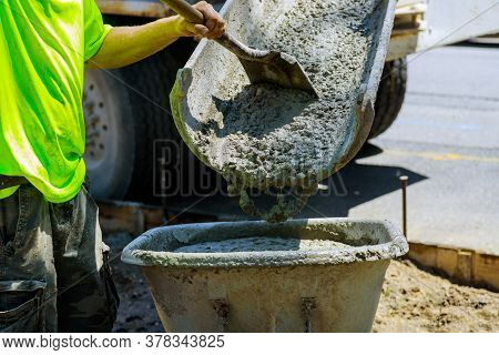 Construction Process Making Of Freshly Poured Cement Wheelbarrow With Shovel Full Of Cement Concrete