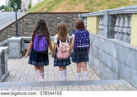 Backs Of Schoolkids With Colorful Backpack Moving In The Street.