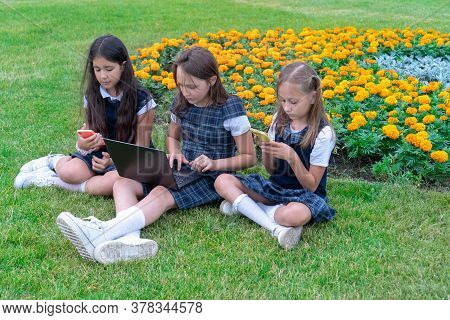Three Schoolgirls In School Uniforms With A Phone And A Laptop Are Sitting On The Grass In The Park