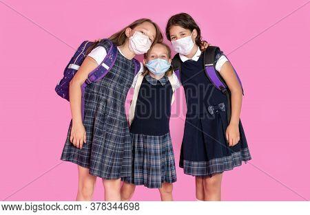 Three Happy Girls With Long Hair In School Uniforms Wearing Medical Masks. Stop Coronavirus. Distanc