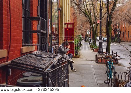 New York City, Usa - February 11, 2020: Young Woman Using Smartphone Sitting On The Street Bench Nea