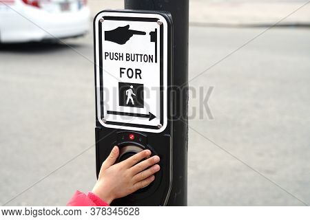 Kids Hand On Pedestrian Sign And Push Button