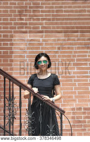 A Chinese Woman Leaning On A Metal Railing With A Red Brick Background, In Qingdao China.