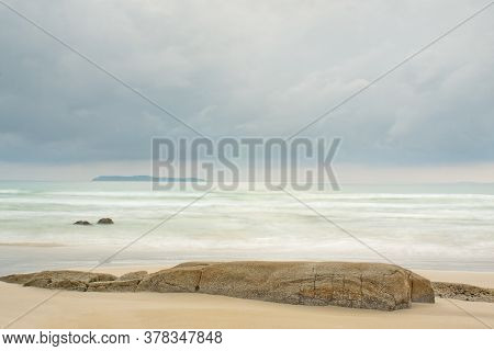 Tranquil Scene Of A Beach At The Sea With An Island In The Background And Rocks In The Foreground