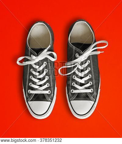 Black Generic Sneakers Isolated On Red Background