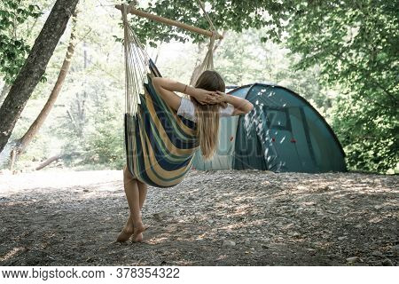 A Young Woman Relaxing In A Hammock. Girl Resting In The Woods, Camping In A Hammock. Healthy Lifest