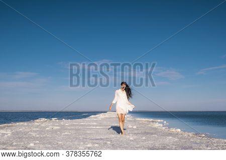 A Beautiful Woman Walks Along The Seashore In A Beach Dress.