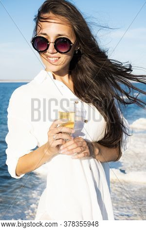 Photo Of A Beautiful Woman By The Sea With A Glass Of Champagne. A Girl In A Beach Dress Drinks Wine