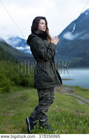 A Woman In A Warm Jacket With Long Hair Stands Against A Background Of Mountains In The Fog In Cold