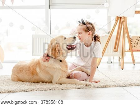 Cheerful little girl having fun with cute dog in playroom