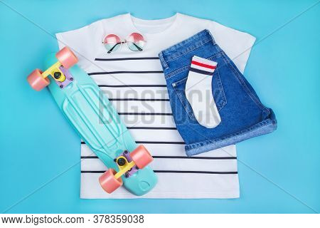 Sport Inspired Flatlay With Turquoise Penny Skateboard, White Striped T-shirt, Socks, Denim Shorts A