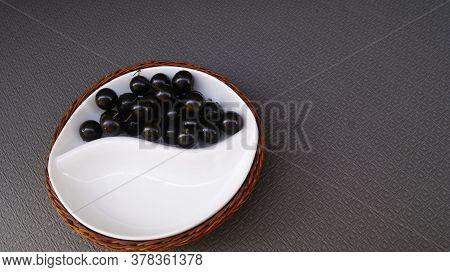 Jabuticaba Fruit, Fruit Of Brazilian Origin, On A Ceramic Plate Supported By A Wicker Basket  Jabuti
