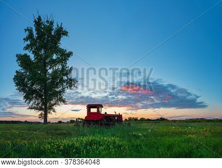 Beautiful Sunset Over Field And Old Rusty Tractor. Hdr