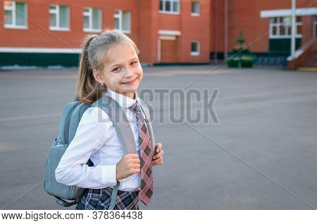 Happy Smiling Girl Goes To The Elementary School. Child With A Grey Backpack And In The Uniform Is G