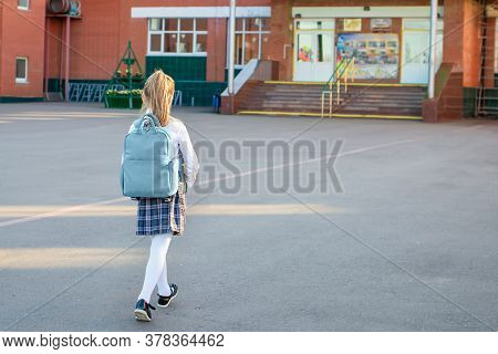 Happy Little Girl Goes To The Elementary School. Child With A Grey Backpack And In The Uniform Is Go