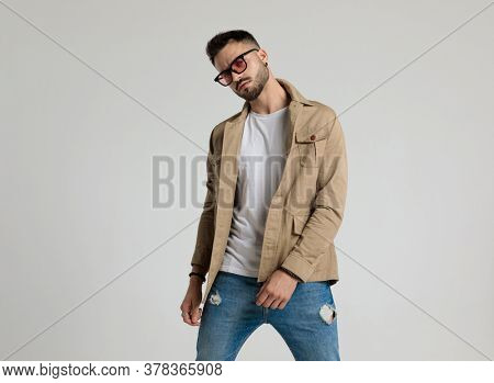 sexy unshaved fashion model in jacket wearing sunglasses and standing in a fashion pose on grey background