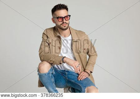 attractive young unshaved man in jacket wearing sunglasses and looking away, holding elbows on knees and crouching on grey background