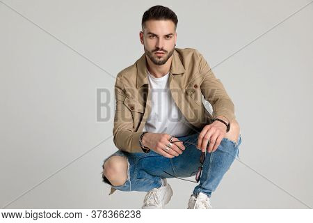 handsome young casual man in jacket, holding elbows on knees, holding sunglasses and crouching on grey background