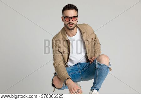 sexy young casual man in jacket wearing sunglasses, holding elbow on knee and posing, crouching on grey background