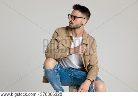 sexy young man in jacket wearing glasses, looking to side, holding elbows on knees and posing, crouching on grey background