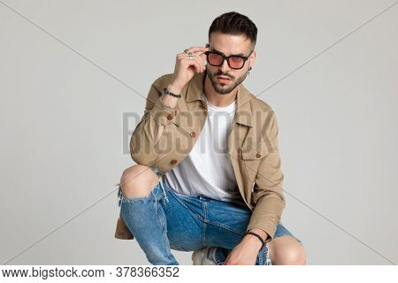 confident young unshaved man in jacket fixing sunglasses, holding elbows on knees and crouching on grey background